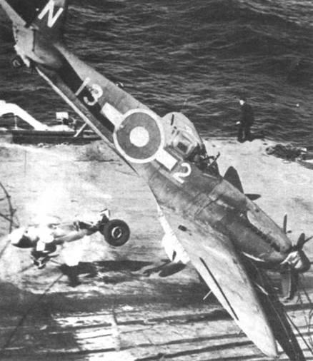 «Сифайр XV» из 801-й эскадрильи пытается произвести посадку на палубу авианосца. Стойка основного шасси и подвесной топливный бак оторваны и отлетают в сторону, сам самолет заснят за мгновение до того, как он перевернулся на палубу кверху «брюхом».