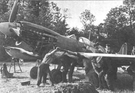 Снимок возможно сделан во Франции на аэродроме Базенвилль, примерно через неделю после вторжения союзников в Нормандию. Во всю идет ремонт «Спитфайра» Mk IX из 403-й «канадской» эскадрильи. По сломанной лопасти винта легко установить, что винт — деревянный.