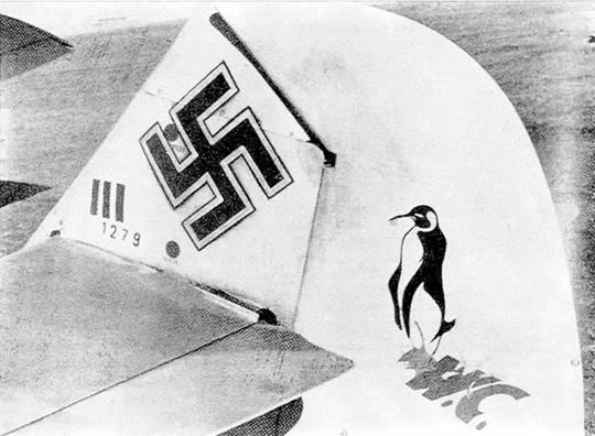 Хвостовая часть <a href='https://arsenal-info.ru/b/book/2753724368/7' target='_self'>Bf 109E</a> Ганса Троицша с обозначениями трех побед, двух пулевых пробоин (черные точки) и эмблемой 6-й эскадрильи – пингвином испражняющимся на инициалы Уинстона Черчилля.