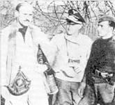 Будущие «эксперты» лейтенант Эрих Хохаген (в центре) и оберлейтенанат Иозеф Фезе (справа) свотографированы рядом с пленным британским пилотом Сесилом Мильне. Его «спитфайр» был сбит оберфельдфебелем Ильнером 21 апреля 1940 г. Позже англичанин вспоминал: «Шесть мессершмиттов сели мне на хвост, по я не замечал их, так как был занят фоторазведкой. Ведущий всадил снаряд в двигатель моего самолета и тот сразу же заглох. Планируя, я пытался дотянуть до своих, но не смог, и сев в одной из деревень, был сразу же арестован.