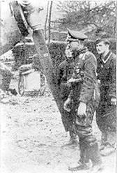 Адольф Галланд осматривает свой истребитель. Напряженный вид техников говорит о том, что не все увиденное его устраивает. Галланд носит трофейные британские «летные штаны Ирвина», III./JG 26, Адамберт, 1940 г.