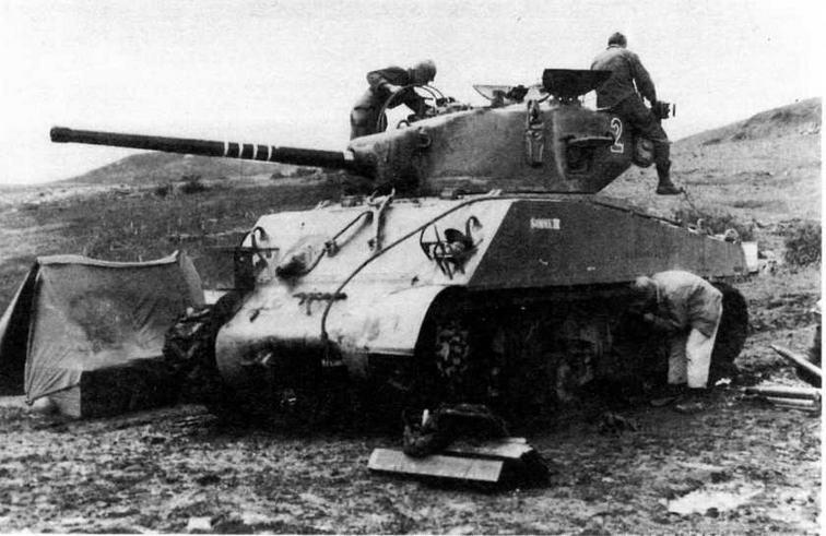 Экипаж танка М4А3(76) W 1-й танковой дивизии занят загрузкой боеприпасов и подготовкой танка к бою перед атакой Болоньи. Италия, 19 октября 1944 года.