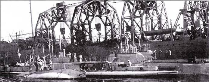 Российская плавучая база Волхов и стоящие у ее борта подводные лодки. На переднем плане видна миниатюрная подводная лодка типа Holland.