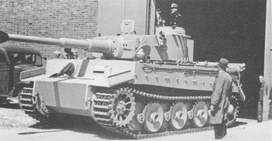 Серийный «Тигр» выезжает из цеха. Машина оснащена узкими транспортными гусеницами; наружный ряд опорных катков демонтирован.