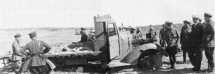 Командный состав штаба 1-й армейской группы, посол Советского Союза в Монголии И. А. Иванов (в костюме и кепке) и главнокомандующий МНРА маршал МНР Х. Чойболсан (слева от Иванова) осматривают разбитый автомобиль Ford V8 американского производства. Сентябрь 1939 года (АСКМ)