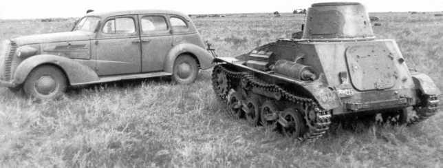 Трофейный японский легкий танк Тип 94 «ТК» 3-го танкового полка Квантунской армии, вид сзади. Видна табличка с военным номером танка — 225. Рядом легковой автомобиль Chevrolet 1938 года модель Master series НА (АСКМ).