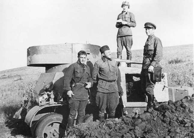 Экипаж броневика БА-6, предположительно из состава 7-й мотоброневой бригады, у своей боевой машины. Июль — август 1939 года. Бронеавтомобиль покрыт слоем пыли, которая стерта вдоль верхней кромки башни (АСКМ).