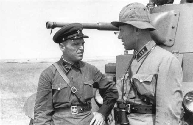 Командиры 6-й танковой бригады обсуждают боевую задачу: слева майор, справа старший батальонный комиссар (фамилии автору неизвестны). Август 1939 года. На заднем плане танк БТ-7 с конической башней (АСКМ)