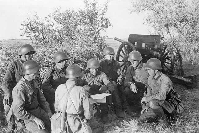 Артиллеристы 175-го артиллерийского полка 36-й моторизованной дивизии читают свежий номер газеты «Героическая красноармейская». 23 июля 1939 года. На заднем плане 76-мм орудие образца 1902/30 года (АСКМ)