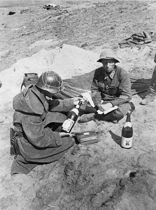 Советские пехотинцы рассматривают трофеи — бутылки с японским сакэ. Август 1939 года. Этот сорт сакэ выпускается до сих пор. Обратите внимание на веревочную сетку на каске одного из бойцов — она служила для крепления веток или травы для маскировки. Глянцевая краска на касках сильно блестела на солнце, сильно демаскируя бойцов. Во избежание этого использовали веревочные сетки для травы или перекрашивали каски матовой краской. У второго бойца на фото каска перекрашена (ЦМВС)
