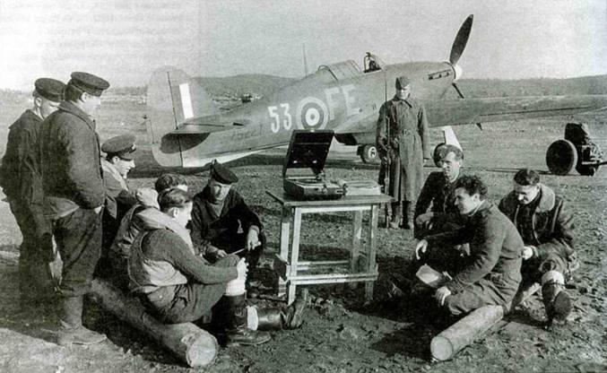 Другой «Харрикейн IIВ», Z5227 из 81-й эскадрильи, аэродром Ваенга. Английские пилоты и механики слушают патефон вместе с советскими механиками. У самолета стоит караульный красноармеец.