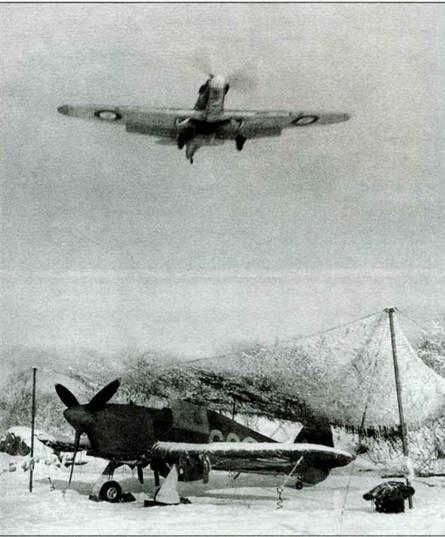 Стоянка самолетов 134-й эскадрильи, Заполярье, ноябрь 1941 года. Над «Харрикейном» растянута маскировочная сеть. Уязвимые части машины закрыты брезентом. В небе пролетает другая машина из той же части.