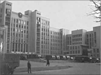 Монументальный дом компартии в Минске. Перед ним стоит много немецких автомобилей. Знамя со свастикой укрывает серп и молот Советов.