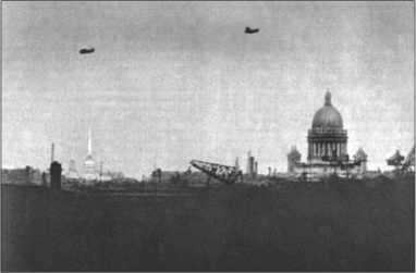 Кадр, снятый немецким фотоаппаратом для дальней съемки,— силуэт Ленинграда, который не должен был быть завоеван, а должен был вымереть от голода. Слева шпиль на башне Адмиралтейства, справа мощный купол Исаакиевского собора и портовые краны.