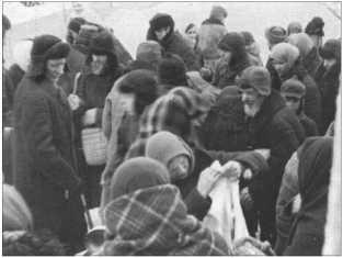 Русское гражданское население, укутанное в теплую зимнюю одежду, на рынке одного русского города.Много купить там все-таки было нельзя.