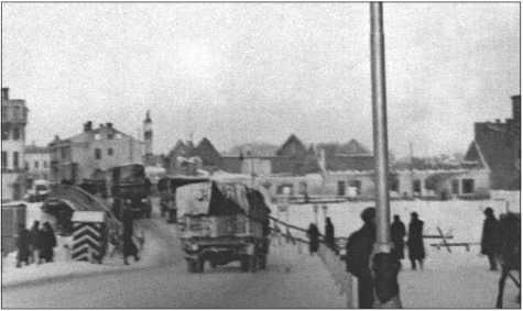 Зима 1941/42 года в Нарве: немецкий караульный домик стоит перед въездом на мост. Грузовики пробиваются вперед по обледеневшей дороге.