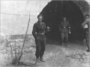 Фельдфебель Гюнтер Хердер из 3-й роты 29-го танкового полка в расслабленной позе перед одними из городских ворот Нарвы.