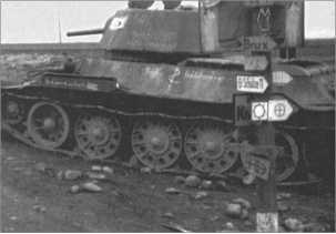 Подбитый русский Т-34/76D, который участвовал в боевых действиях начиная с середины 1942 года.Столб с дорожными указателями показывает направление к частям 13-й танковой дивизии.
