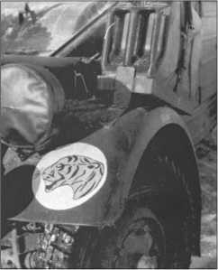 Тактический знак 503-го тяжелого танкового батальона (до начала 1943 года), тигровая голова на белом фоне. Он нарисован на левом крыле одного из кюбель-вагенов батальона.