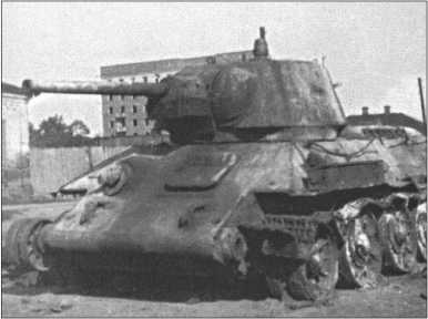 На городских пейзажах Харькова все еще видны следы боев за город в начале 1943 года, когда наш батальон еще был на Миусе. Здесь сгоревший Т-34/76D, который потерял свои гусеницы.