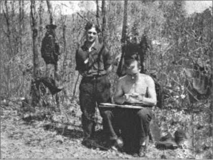 Хотя в лесу у Толоконое на деревьях еще нет листьев, солнце уже пригревает. Альфред Руббель с планшетом с картами, рядом с ним стоит товарищ Вальтер Юнге.