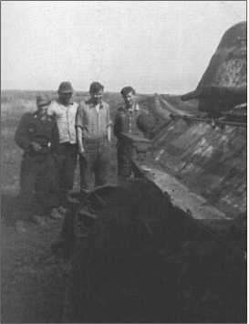 Херберт Бёме, унтер-офицер Риппль, Биндер и еще один товарищ из 1-й роты 503-го тяжелого танкового полка осматривают подбитый Т-34. Один из катков Т-34разбит попаданием снаряда.