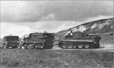 114-го «Тигра» тащат на прицепе два 18-тонных тягача Фамо. «Тигр» соединен с тягачом тягой. Первый тягач соединен со вторым стальным тросом.