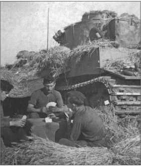 «Тигр», замаскированный соломой, его экипаж перед ним играет в скат.Солдат посередине — это Ханс Вельш.