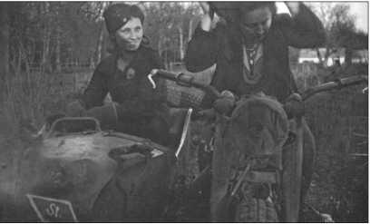 Обе украинки, Хала и Мария, могут проехать пару кругов на мотоцикле с коляской штабной роты, что их явно радует.