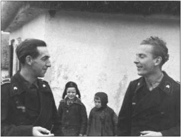 Фанен-юнкер-фельдфебель Ханс Левандовски (слева на фотографии) разговаривает с неизвестным унтер-офицером.Оба русских мальчика на заднем плане уже в зимней одежде. Левандовски погиб, будучи лейтенантом, в 1945 году в 509-м «тигровом» батальоне.