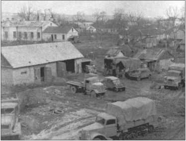 Вид с крыши дома в Таврове на часть автомобильного парка ремонтной роты батальона. Кроме грузовиков «Богвард» и «Фольксваген-Кубельваген»снизу справа еще виден «Форд-Мул», у которого вместо задней оси была простая гусеничная ходовая часть. В украинской грязи они были гораздо лучше, чем обычные колесные грузовики.