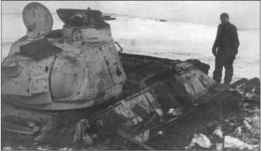 Фельдфебель Эрдманн осматривает окопанный Т-34-76 последней серии, по немецкому образцу оснащенный командирской башенкой с круговым обзором. Фотография была снята в Оратофф.
