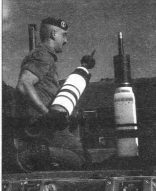 Французский солдат загружает в «Леклерк» боеприпасы. В его руках выстрел с подкалиберным снарядом. Рядом стоит выстрел с кумулятивным снарядом