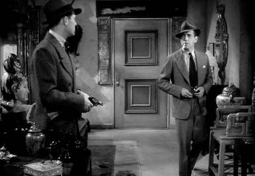 Джон Риджли, сыгравший Эдди Марса, с Colt Detective Special, и Хэмфри Богарт в роли частного детектива Филипа Марлоу в фильме Ховарда Хоукса «Глубокий сон», 1946 года. Один из лучших фильмов в жанре «Нуар», снятый по роману Рэймонда Чэндлера.