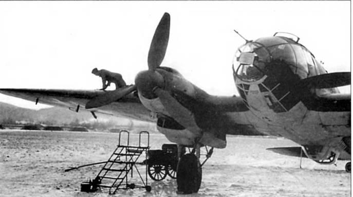 Техник лазает по плоскости крыла бомбардировщика Не-111Н-6. Снимок сделан на аэродроме в Норвегии. На самолеты установлены деревянные воздушные винты с широкой хордой лопасти Юнкере VS-11, на более ранних Не-111 ставили металлические винты VDM с узкими лопастями. Винты с широкими лопастями обладали лучшими характеристиками на больших высотах полета. Использование дерева в качестве конструкционного материала – вынуо/сденпая мера по причине нехватки металла.