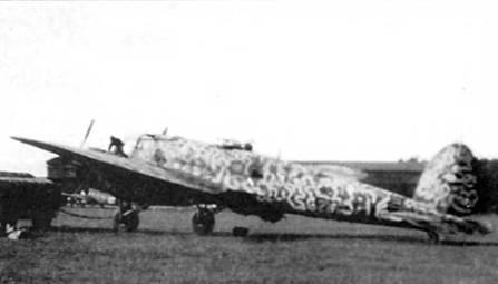 """Не-111Н-21 из KG-4 """"General Wever"""" заправляют горючим па венгерском аэродроме, конец лета 1944 г. На фюзеляже за опознавательным знаком нанесены литеры «В» (красного цвета) и «V» (черного цвета). Поверх стандартного камуфляжа нанесены затейливые линии светло-серого цвета (RLM-76). В подфюзеляжной гондоле стоит 13-мм пулемет MG-131. Скорострельность пулемета 900 выстрелов в минуту, начальная скорость пули – 2370 м/с."""