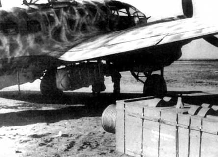 Подвеска 700-кг грузового контейнера под фюзеляж Не-111Н-6 из KG-4, Восточный фронт, 1943 г. Второй контейнер ожидает подвески. Грузовые контейнеры сбрасывались с самолетов на парашютах. Поверх стандартного камуфляжа нанесен «разрушающий» узор светло-серой краской RLM-76.