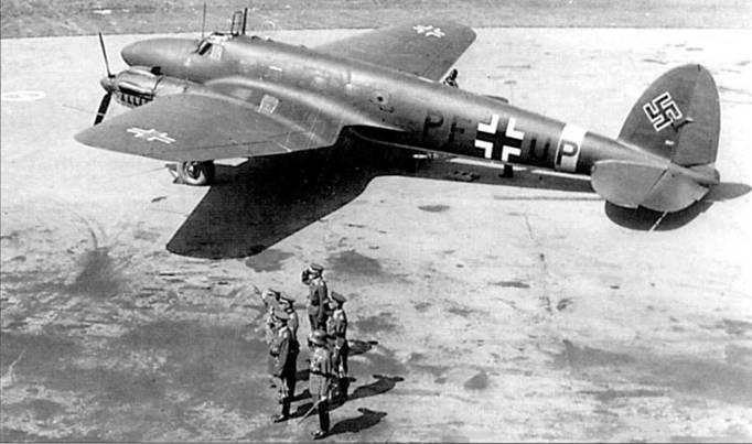 Самолет He-111G-5 (PF+UP) доставил германскую военную делегацию на аэродром Будаёрс, Венгрия. Снимок сделан в промежутке между 1941 и 1944 г.г. Из левого заднего окна фюзеляжа демонтирован оборонительный пулемет MG-15. Верхние поверхности самолета камуфлированы красками RLM-70 (FS 34050, черно-зеленая) и RLM-71 )FS 34079, темно-зеленая), полоса вокруг фюзеляжа – RLM-27(FS 33637, желтый)- Бортовой код написан черной краской (RLM-22, FS 37038), нижние поверхности планера – RL.M- 65 (FS 35352, светло-голубой).