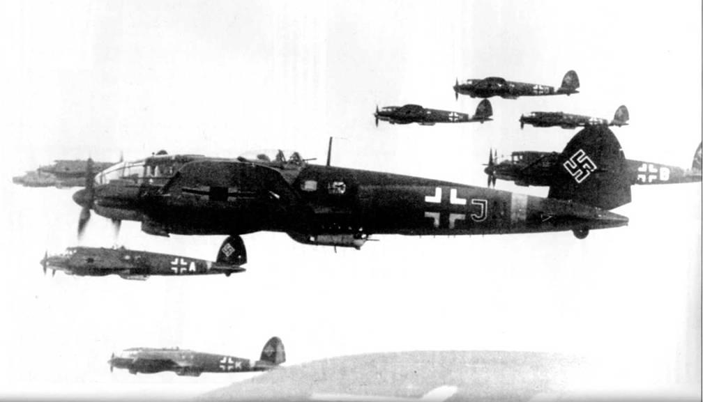 Группа бомбардировщиков Не-111Н-16а на маршруте к целям. Восточный фронт, лето 1941 г. Самолеты принадлежат KG-53. Нижние поверхности концевых частей плоскостей крыла окрашены в желтый цвет RLM-27 (FS 33637), такого же цвета полосы вокруг фюзеляжей. Такая идентификационная окраска характерна для самолетов люфтваффе, действовавших на Восточном фронте. Буква «J» на фюзеляже ближайшего к объективу фотоаппарата бомбардировщика – идентификационная литера стаффеля.