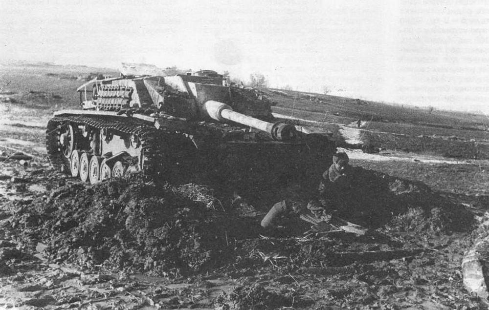 """Прикрываясь корпусом подбитой немецкой САУ StuG 40 Ausf G красноармейцы оборудовали укрытие. Эта машина оснащена """"восточными гусеницами"""" — Ostkette. 1944 год"""