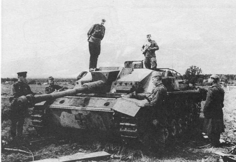 Красноармейцы осматривают <a href='https://arsenal-info.ru/b/book/2435493365/3' target='_self'>штурмовое орудие</a>, подорванное финским экипажем. Июнь, 1944 года