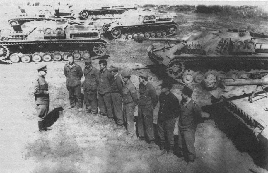 Советский офицер инструктирует немецких механиков-водителей штурмовых орудий StuG IV, захваченных в исправном состоянии при капитуляции Курляндской группировки противника. 1945 год