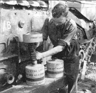 один из членов экипажа готовит к выстрелу 26-фунтовую бомбу, получившую у английских солдат прозвище ялетающий мусорный ящикa