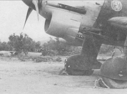 Бомбардировщик Ju-87R-2 из 2./St.G-3 сфотографирован на аэродроме в Греции; на заднем плане — обломки самолетов RAF.
