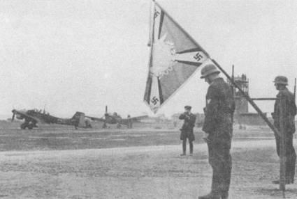 Помпезные церемонии на аэродромах люфтваффе с выносом знамени не являлись уж очень большой редкостью, особенно если предстояла пропагандистская фотосъемка; представители ведомства Геббельса также часто посещали авиационные подразделения. Ближайший к объективу фотокамеры Ju-87B-2 имеет бортовой код «2F+CA».