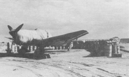 Условия базирования самолетов в Северной Африке иначе как примитивными не назовешь. На снимке — зачехленный бомбардировщик Ju-87R-2/Trop. Чехлы являлись обязательной принадлежностью каждого самолета, как правило чехлы маркировались по заводскому номеру или идентификационному бортовому коду конкретного самолета (дабы не «спионерили»).