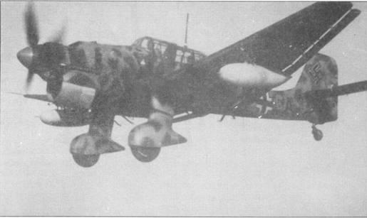 Верхние и боковые поверхности бомбардировщика Ju-87R-2/Trop «2F+CA» основательно покрыты камуфляжными пятнами зеленого цвета. Базовая окраска — желто-песочная. В Северной Африке «Штуки» чаще всего использовались для налетов на передовые позиции британских войск, поэтому 300- литровые подвесные баки на Ju-87R применяли крайне редко. Обратите внимание на выступающие в нижней части фюзеляжа «рога» антенн радиостанции FuG-25.