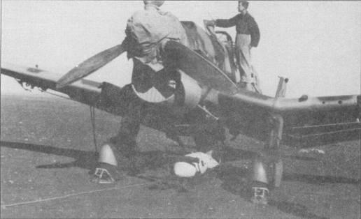Подвеска бомба на подфюзеляжную раму; из-за нехватки транспортеров-подъемников подвеску производили при помощи блока. Механик проверяет уровень масла в маслобаке. Обратите на небольшое отверстие в кромке левой плоскости крыла (ближнее к пулемету)— это объектив фотокинопулемета. На снимке — Ju-87B-2/Trop.
