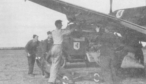 Техники из 7,/St.G-l при помощи трехколесной тележки-подъемника подвесили бомбу SC-250 под плоскость крыла Ju-87. Как правило эмблемы подразделений в люфтваффе наносились не только на самолеты, но и на автотехнику. На заднем плане виден топливозаправщик Опель, на дверь кабины которого нанесена эмблема.