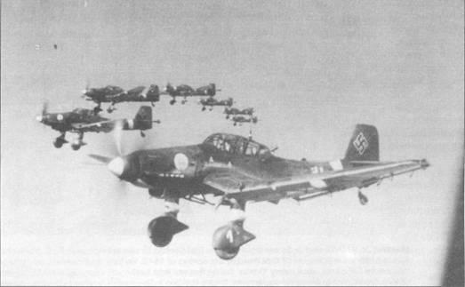 Группа самолетов Ju- 87D-1 из lI/St.G-2 возвращаются с боевого задания. Цифры на обтекателях колес основных опор шасси дублируют идентификационную букву самолета (самолет «T6+AD» имеет цифру «1», «T6+BD» — «2», «Т6+CD» — «3» и т.д.). Данная система дублирования, однако не являлась общепринятой.